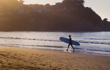 Surfer Walking Along The Beach
