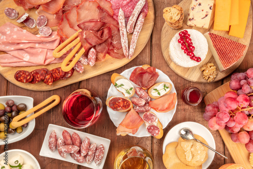 Poster Assortiment Charcuterie Tasting. A photo of many different sausages and hams, deli meats, and a cheese platter, shot from above on a rustic background with a glass of red wine, olives and grapes