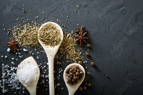Wooden spoon with Italian seasoning-dried oregano with thyme vegetables.Oregano in a wooden spoon on a rocky concrete dark black background with a place for text.Top view.salt crystals pepper
