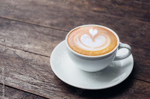 Fotomural Close up white coffee cup with heart shape latte art on grunge wood table at cafe