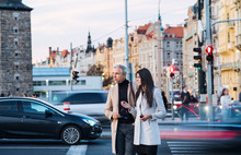 Man And Woman Business Partners Crossing A Busy Road In City Of Prague.
