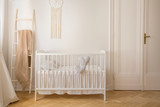 Scandinavian nursery with white wooden crib and macrame on the wall in tenement house, real photo with copy space