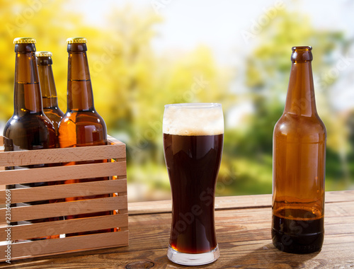 Foto op Aluminium Bier / Cider cup of dark beer and bottles on wooden box on table on blurred park background