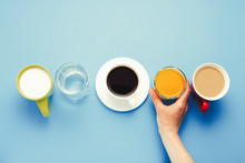 Female Hand Takes A Glass Of Orange Juice Group Of Useful Drinks, Orange Juice, Coffee With Milk, Black Coffee, Just Water, Yogurt On A Blue Background. Flat Lay Still Life Table Top View