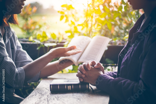 Valokuva  Asian girls are reading the sacred scriptures by pointing to the text of the book