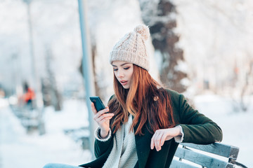 Fototapeta Young woman smiling with smart phone and winter landscape .