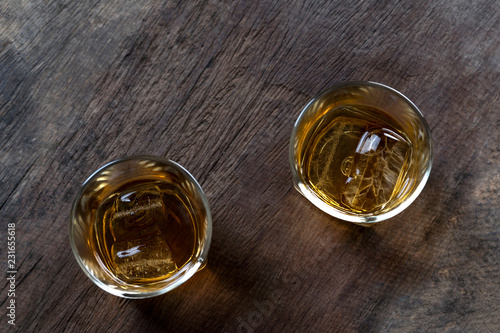 Foto op Aluminium Bier / Cider Top view of Whiskey with ice in glass on wooden table