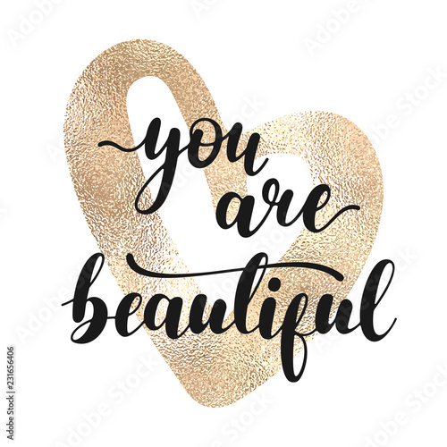Photo  You are beautiful - black hand written lettering with golden heart shape isolated on white background