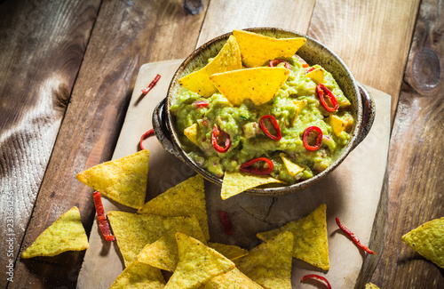 Bowl guacamole corn chips wooden table