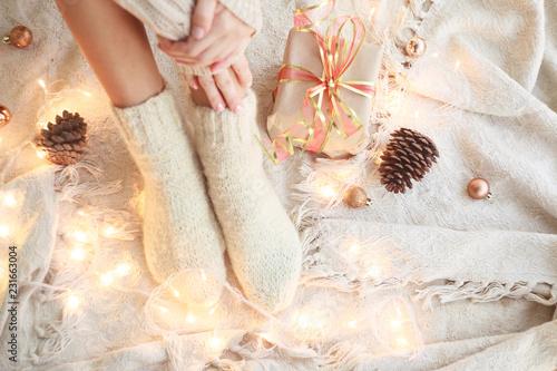 Fotografia  New Year's concept. Women's legs in white wool socks.