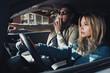 shocked man showing direction to girlfriend on drivers seat in car