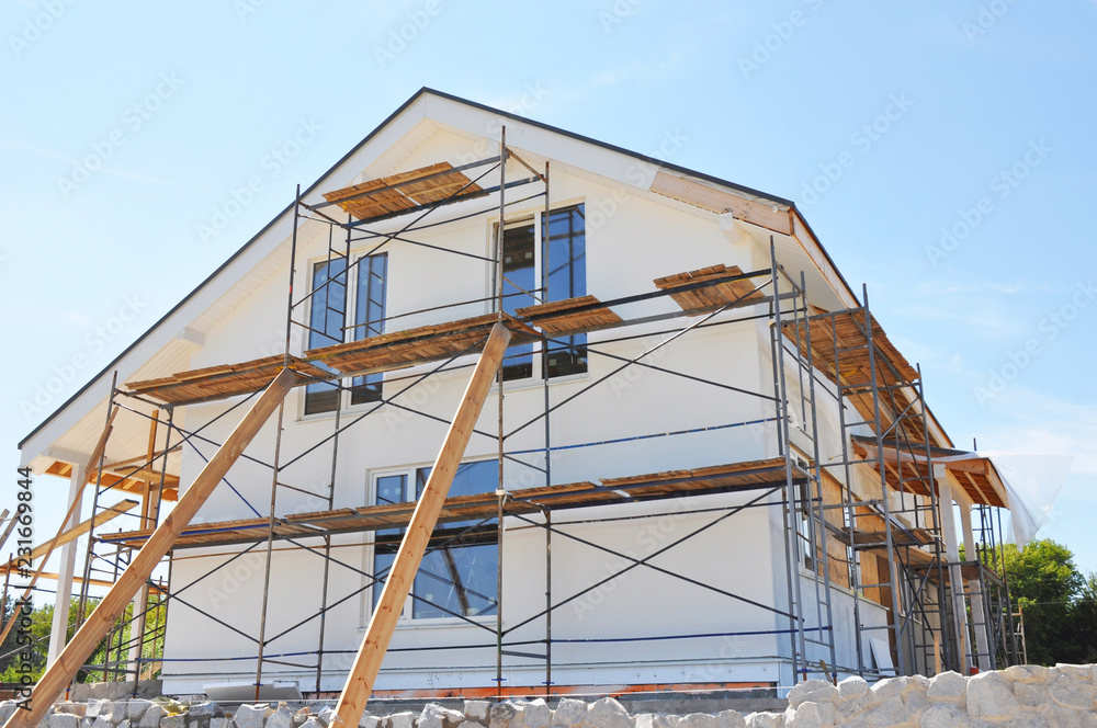Fototapeta Painting, insulatin and plastering facade house walls after home renovation and remodel