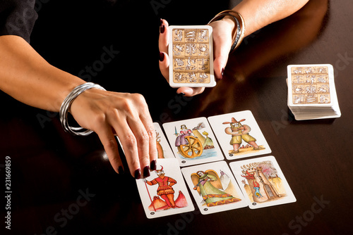 Fototapeta Fortune teller reading a deck of Tarot Cards