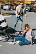 selective focus of injured woman on road after car accident with car driver behind