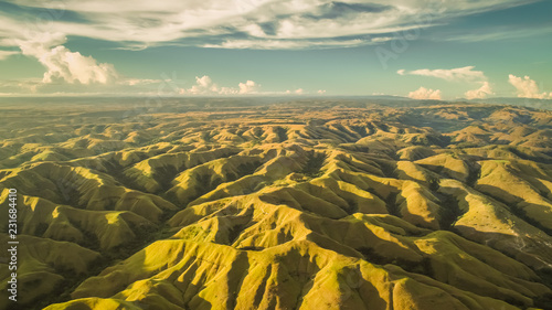 Poster de jardin Colline Aerial panorama green hills. Drone shot. Indonesia. Breathtaking landscape hilly surface on the blue cloudy sky background. Sumba island. Magnificient beauty of wild virgin nature.