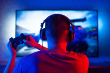 Rear View Of A Young Player Playing Video Games On An FPS Console At Home