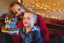 Mother And Son Holding Christmas Tree Snow Globe At Home