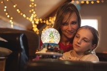 Mother And Daughter Looking At Christmas Tree Snow Globe
