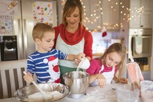 Mother And Kids Preparing Dough To Make Christmas Cookies