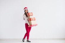 Christmas And Holidays Concept - Young Woman In Santa Hat Holding Stack Of Gift Boxes Over White Background With Copy Space