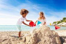 Cute Boy And Girl Building Sandcastle On The Beach