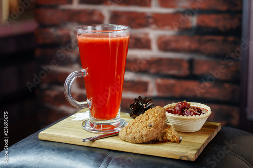 Delicious drink in a mug with cookies and strawberries in a basket on a wooden board