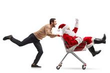 Young Man Pushing Santa Claus Inside A Shopping Cart