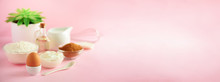 Healthy Baking Ingredients - Butter, Sugar, Flour, Eggs, Oil, Spoon, Brush, Whisk, Milk Over Pink Background. Banner. Bakery Food Frame, Cooking Concept With Succulent Plant. Copy Space.