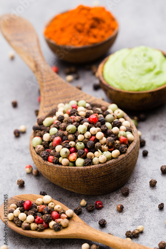 Foto op Canvas Kruiderij Peppercorn mix in a wooden bowl on grey table.