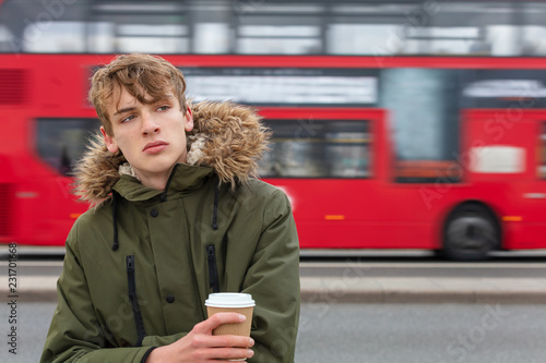 Fotografie, Obraz  Male Young Adult Teen Drinking Coffee By Red London Bus