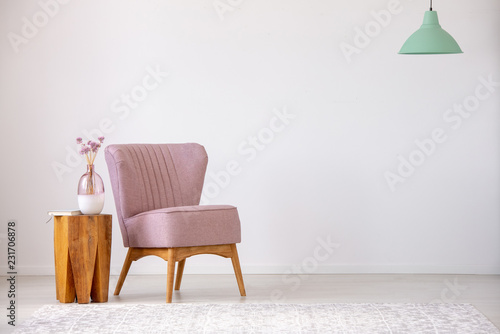 Tela Flowers on wooden stool next to pink armchair in flat interior with copy space and mint lamp