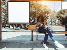 A Smiling Caucasian Female With Bulky Curly Hair And In Eyeglasses Is Sitting Inside Of The Outdoor Bus Stop And Using Her Smartphone With An Empty White Mockup Of Information Billboard Next To Her