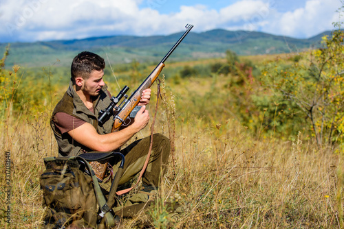 Hunter with rifle looking for animal. Hunting hobby and leisure. Man charging hunting rifle. Hunting equipment concept. Hunter khaki clothes ready to hunt nature background. Hunting shooting trophy