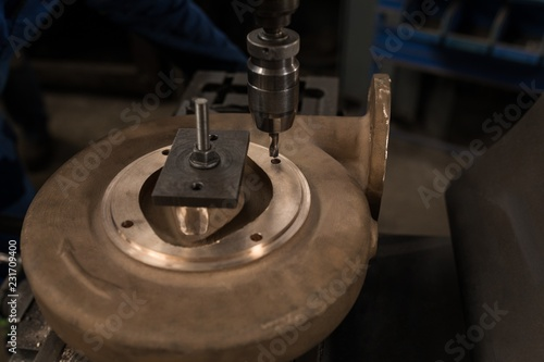 Press drill and metal piece in workshop