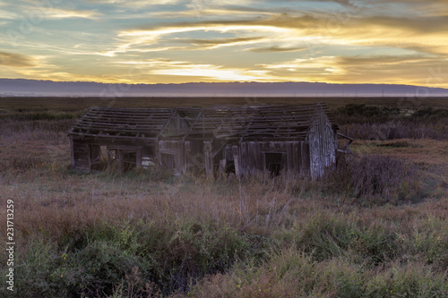Photo Sunset over abandoned house at Drawbridge, the last remaining ghost town in San Francisco Bay Area