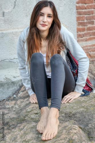 Fotografie, Obraz  Ritratto di una ragazza seduta a terra con i piedi nudi