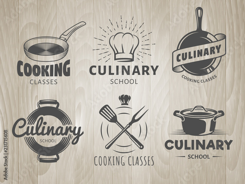 Fototapeta Culinary school logos. Vector labels for cooking classes, workshops and courses. Set of monochrome badges with chefs hat, pans and kitchenware on vintage wooden background obraz