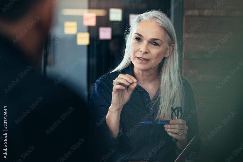 Fototapeta Mature business woman advising her colleagues in meeting