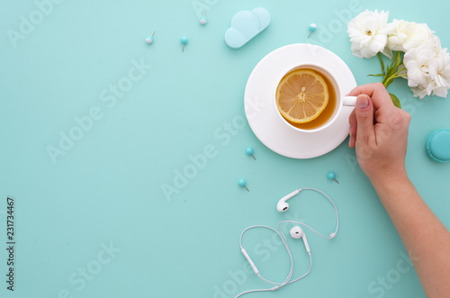 girl holds morning tea with lemon in her hands on a mint tiffany background with white roses earphones and office supplies Wallpaper Mural