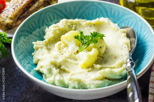 Mashed cauliflower with oil in blue bowl on wooden table.