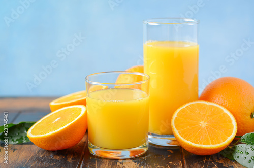 Fresh orange juice in a glasses on old wooden table, selective focus.