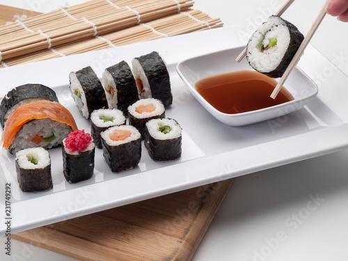 Photo Bandeja con resultados de sushis y uno con palillos en primer plano
