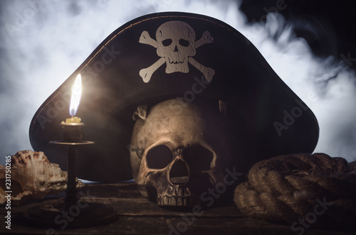 Fotografija  Human skull with pirate captain hat above, burning candle, seashell and mooring rope on the wooden table in the mystic smoke