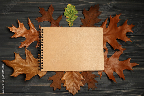 autumn leaves and paper notebook on wooden background with copy space for text