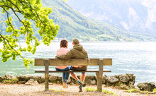 Happy Couple Sitting On The Wooden Bench