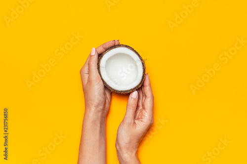 Female hands holding ripe coconut on yellow colored background, minimal flat lay style top view with copy space. Pop art design, creative summer, food concept. Tropical fruit whole and half abstract