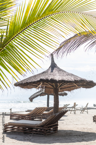 Beach chairs on a thatch palapa umbrella on a beach