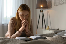 Religious Young Woman Praying Over Bible In Bedroom