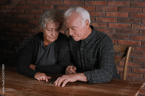 Fényképezés  Poor elderly couple counting coins at table