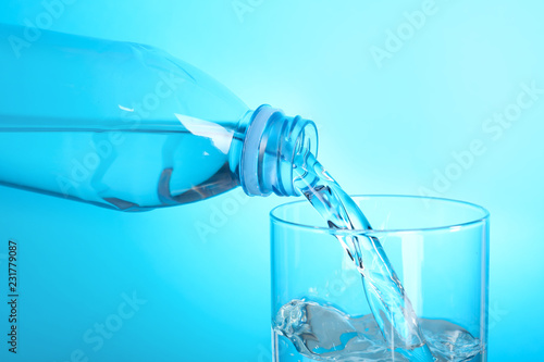Staande foto Water Pouring water from bottle into glass on color background